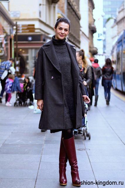 Трикотажное теплое платье серого цвета на работу, длиной до колен в сочетании с высокими бордовыми сапогами.