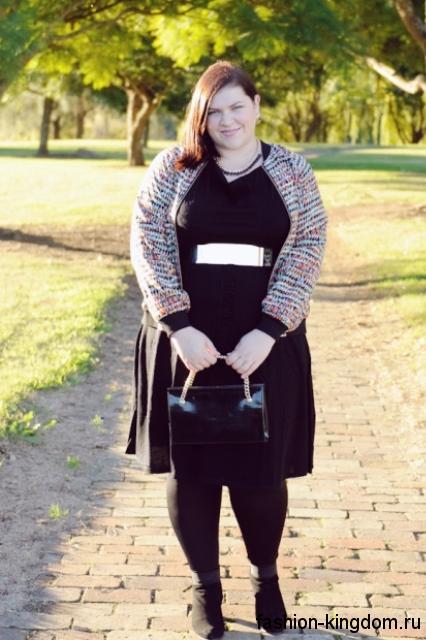 Теплое платье черного цвета для полных женщин, полуприталенного кроя, длиной чуть ниже колен, с серебристым поясом.