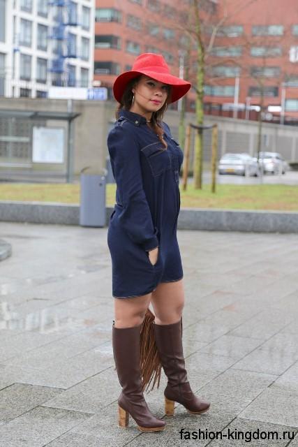 Джинсовое теплое платье синего тона для полных, прямого покроя, длиной выше колен в тандеме с высокими сапогами.