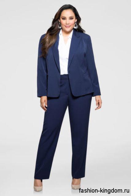 Классический брючный костюм темно-синего цвета для полных женщин сочетается с белой блузкой.