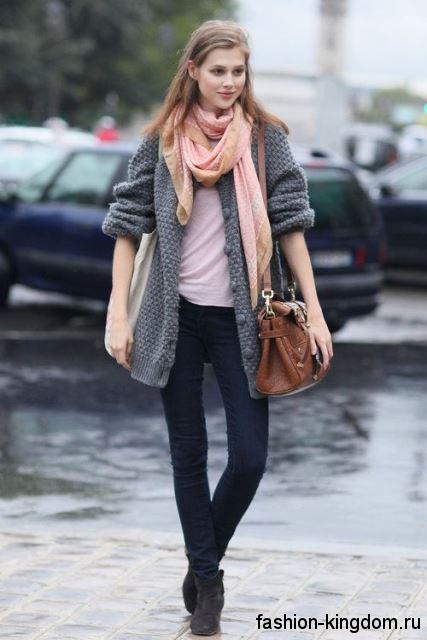Вязаный кардиган серого цвета, средней длины, на пуговицах в сочетании с узкими темными джинсами.