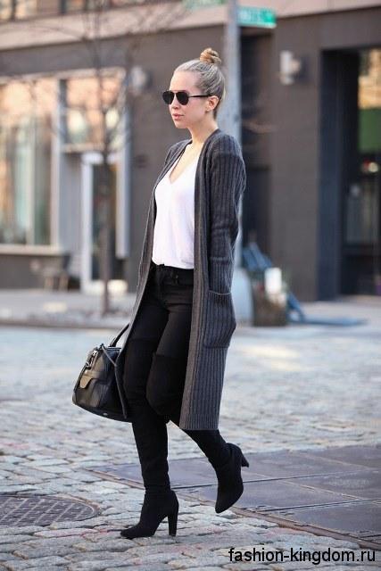 Длинный кардиган темно-серого цвета с накладными карманами сочетается с белой блузой и узкими черными брюками.
