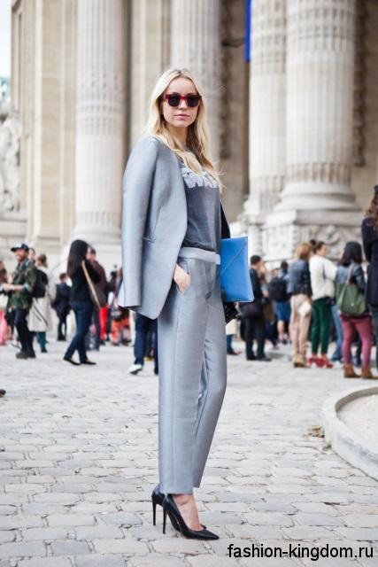 Деловой брючный костюм серебристого цвета, прямого кроя сочетается с серой блузой и туфлями на шпильке.