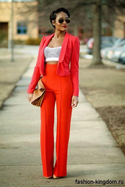 Красный брючный костюм в виде брюк с завышенной талией и короткого пиджака, дополненного белым топом.