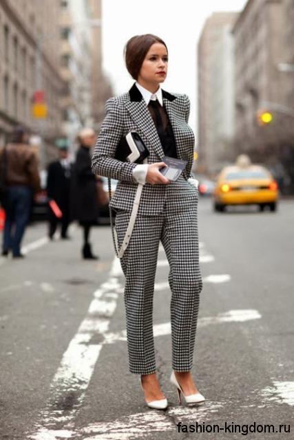 Офисный женский брючный костюм черно-белого цвета в клетку, прямого фасона в тандеме с белыми туфлями на каблуке.
