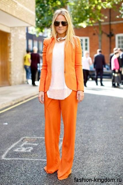 Брючный женский костюм оранжевого цвета сочетается с белой шифоновой блузкой.