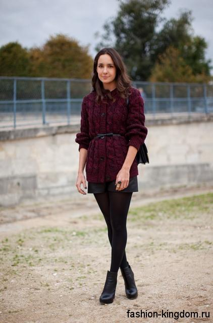 Вязаный теплый кардиган на пуговицах, бордового цвета, с кожаным пояском сочетается с короткой юбкой и ботильонами на каблуке.