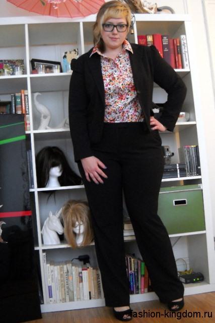 Офисный брючный костюм черного цвета для полных женщин сочетается с блузкой цветочной расцветки.