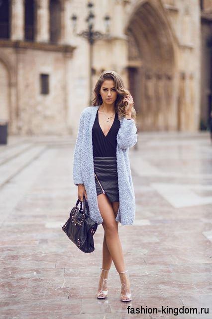 Женский длинный кардиган голубого цвета сочетается с асимметричной короткой юбкой и черной блузкой.