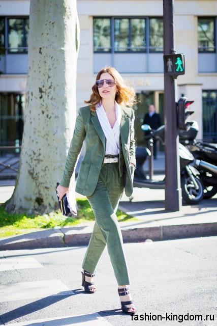 Женский брючный костюм зеленого цвета в виде прямых брюк и длинного пиджака сочетается с белой блузкой и босоножками на каблуке.