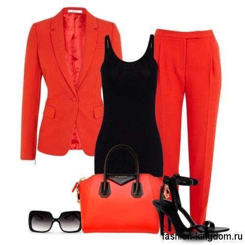 Женский брючный костюм красного цвета, классического фасона сочетается с черной майкой и босоножками на каблуке.