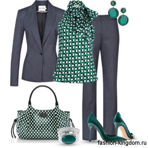 Офисный женский брючный костюм темно-серого цвета в сочетании с блузкой бело-зеленой расцветки без рукавов.