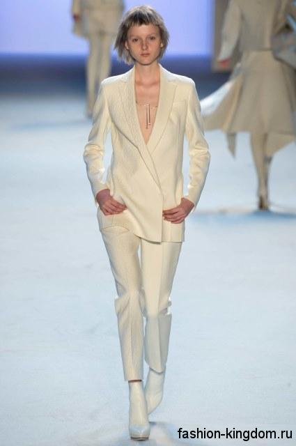 Белый брючный костюм в виде укороченных брюк и длинного пиджака в тандеме ч ботильонами на каблуке от Akris.