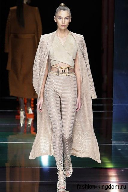 Кардиган бежевого цвета длиной ниже колен, с фактурным рисунком в тандеме с узкими брюками от Balmain.