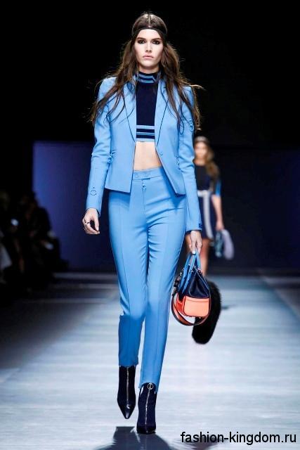 Стильный брючный костюм голубого цвета, приталенного кроя в тандеме с темно-синим топом от Versace.