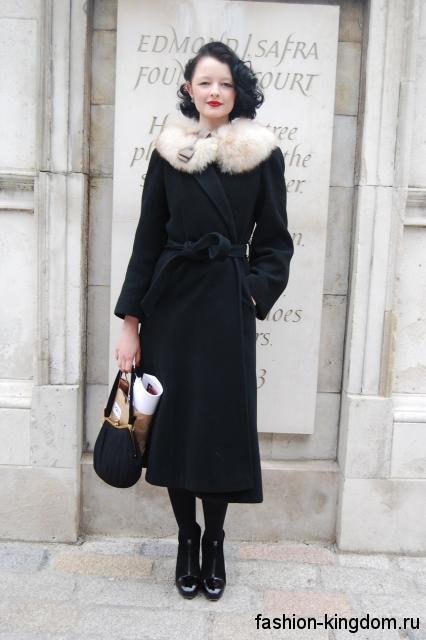 Осеннее пальто черного цвета в стиле 30-х годов, прямого кроя, с меховым воротником и тонким поясом.