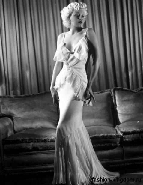 Шифоновое платье 30-х годов длиной в пол, белого цвета, с глубоким декольте и оборками.