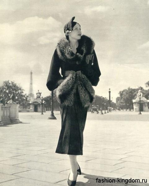 Женское пальто черного цвета 30-х годов, длиной ниже колен, приталенного кроя, с меховым воротником.