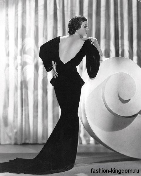 Вечернее черное платье со шлейфом 30-х годов, приталенного фасона, с открытой спиной и широкими рукавами.