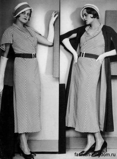 Небольшая шляпка с широкой лентой 1930-х годов дополняет длинное платье черно-белого цвета в полоску, прямого покроя.