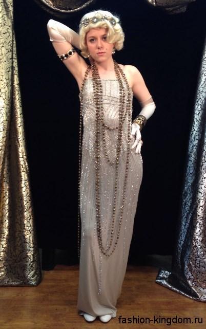 Вечернее длинное платье серебристого цвета в стиле 30-х годов, из блестящей ткани, приталенного кроя, без рукавов.