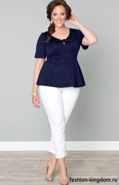 Атласная блузка темно-синего цвета с короткими рукавами для полных женщин сочетается с белыми брюками.