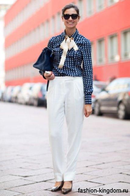 Офисная блузка темно-синего цвета в белый горошек, с длинными рукавами и галстуком в тандеме с белыми брюками.