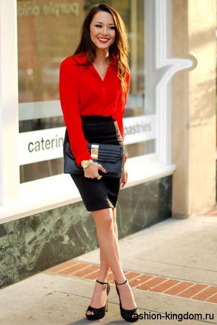 Блузка красного цвета с длинными рукавами сочетается с черной юбкой-карандаш и открытыми туфлями.