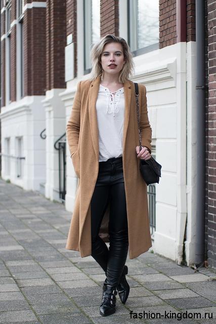Белая блузка со шнуровкой на осень сочетается с пальто бежевого цвета черными брюками.