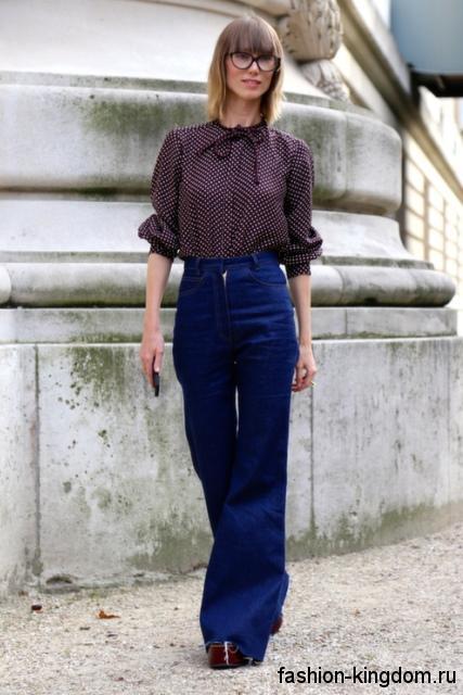 Блузка темно-сливового оттенка в мелкий горошек, с длинными рукавами в сочетании с джинсами-клеш.