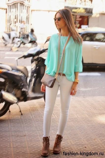 Шифоновая блузка бирюзового цвета, свободного фасона, с рукавами до локтей в сочетании с узкими белыми брюками.