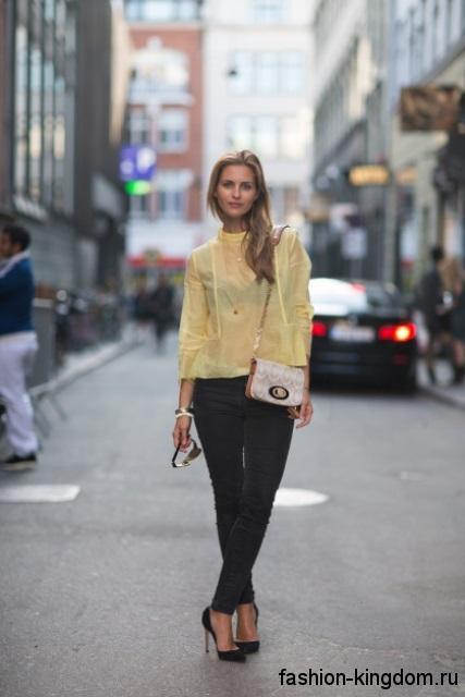 Полупрозрачная желтая блузка прямого кроя, с рукавами три четверти сочетается с узкими черными брюками.