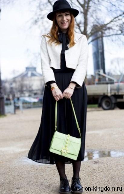 Черная блузка с длинными рукавами и галстуком сочетается с шифоновой черной юбкой-миди.