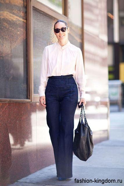 Классическая блузка белого цвета с длинными рукавами сочетается с джинсовыми брюками прямого кроя.