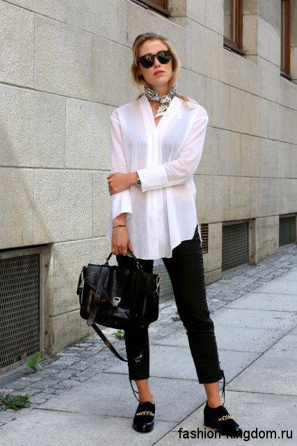 Длинная блузка белого цвета, свободного кроя, с длинными рукавами в сочетании с укороченными черными брюками.