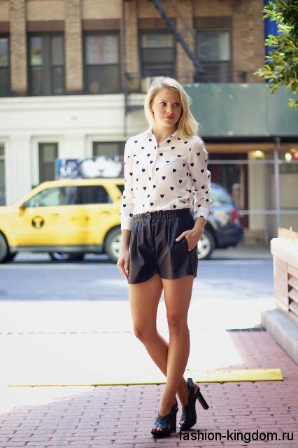 Тонкая блузка белого цвета с черным принтом, с длинными рукавами сочетается с кожаными шортами черного тона.