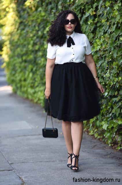 Шелковая блузка белого цвета, с короткими рукавами и черным галстуком для полных в тандеме с пышной черной юбкой.