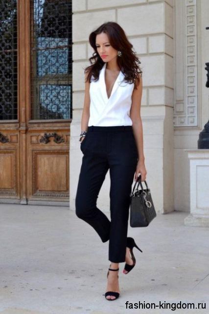 Белая блузка без рукавов, прямого кроя, с V-образным вырезом сочетается с короткими черными брюками.