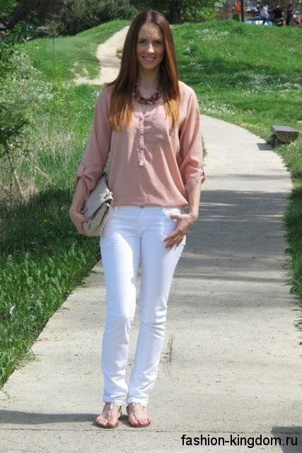 Легкая блузка бежевого цвета, с рукавами три четверти, свободного кроя в тандеме с узкими белыми брюками.