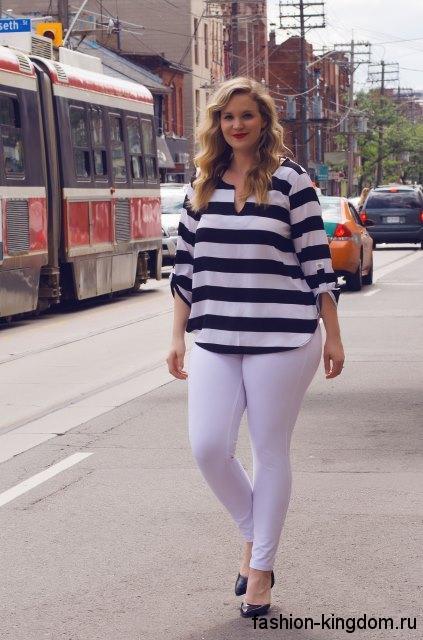 Летняя блузка черно-белого цвета в полоску, с рукавами три четверти для полных сочетается с узкими белыми брюками.