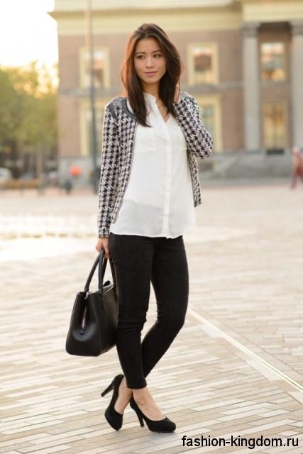 Офисная блузка белого цвета, прямого фасона гармонирует с черными узкими брюками.