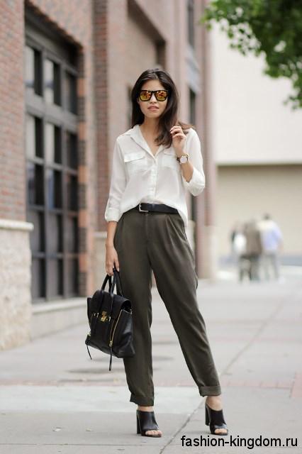 Летняя белая блузка прямого фасона, с рукавами три четверти и накладными карманами сочетается с темно-серыми брюками.