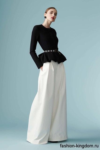 Черная блузка с баской и длинными рукавами в тандеме с широкими белыми брюками из коллекции Carolina Herrera.
