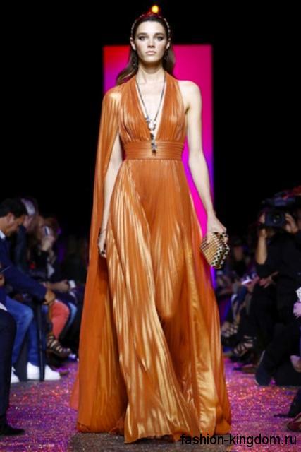 Вечернее платье в пол рыжего цвета, с плиссированной юбкой, V-образным вырезом и акцентом на талии от Elie Saab.