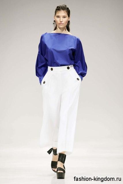 Короткие брюки белого цвета, широкого покроя в сочетании с блузой синего тона с длинными рукавами от Escada.
