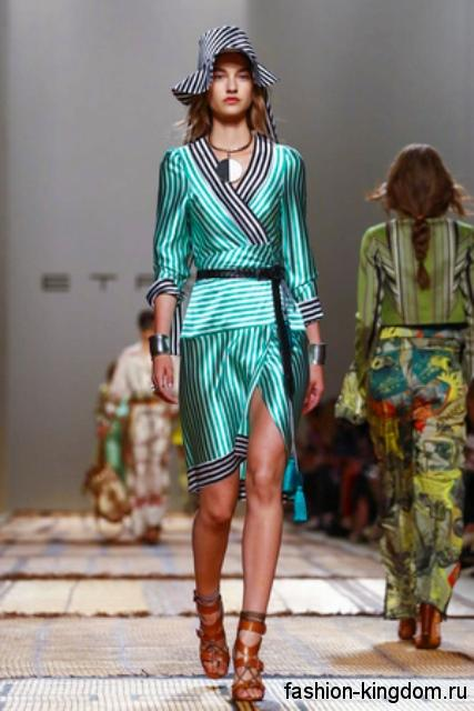 Коричневые босоножки на каблуке, крупные украшения и полосатая шляпа дополняют платье бирюзового цвета от Etro.