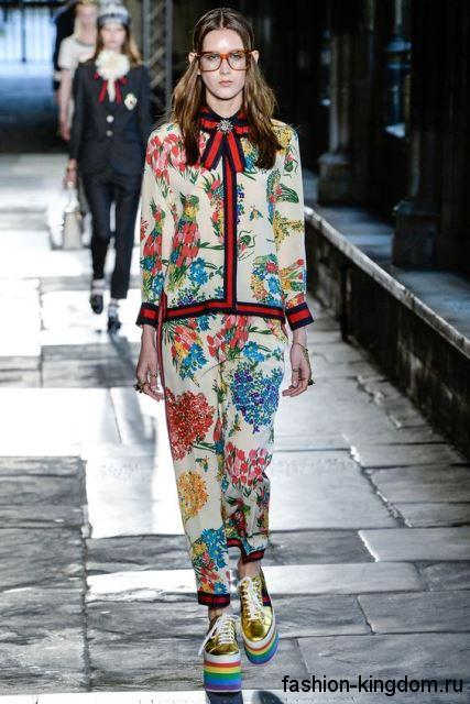 Белый брючный костюм с цветочным рисунком, прямого покроя в сочетании с туфлями на платформе от Gucci.