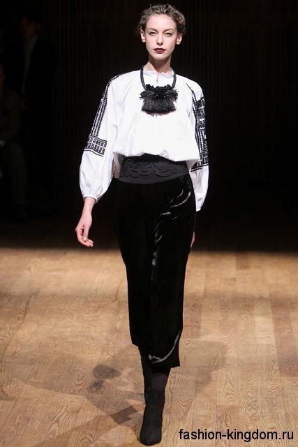Белая блузка с черным рисунком в стиле этно, с рукавами три четверти в сочетании с черной юбкой-миди от Josie Natori.