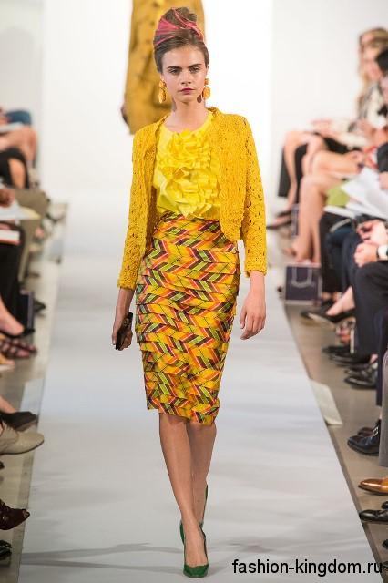 Атласная блузка желтого цвета с жабо в сочетании с юбкой-миди желтого тона с принтом из коллекции Oscar de la Renta.