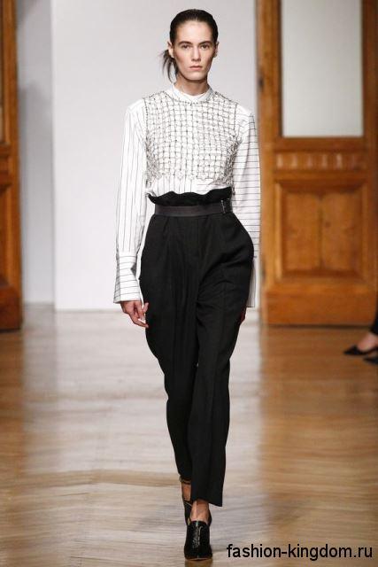 Белая блузка с черным полосатым принтом, прямого кроя, с длинными рукавами в тандеме с черными брюками от Rimondi.